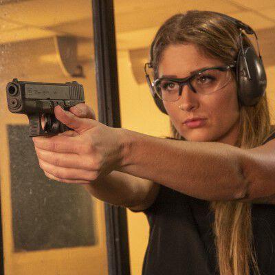 Lady pointing a handgun in an indoor range