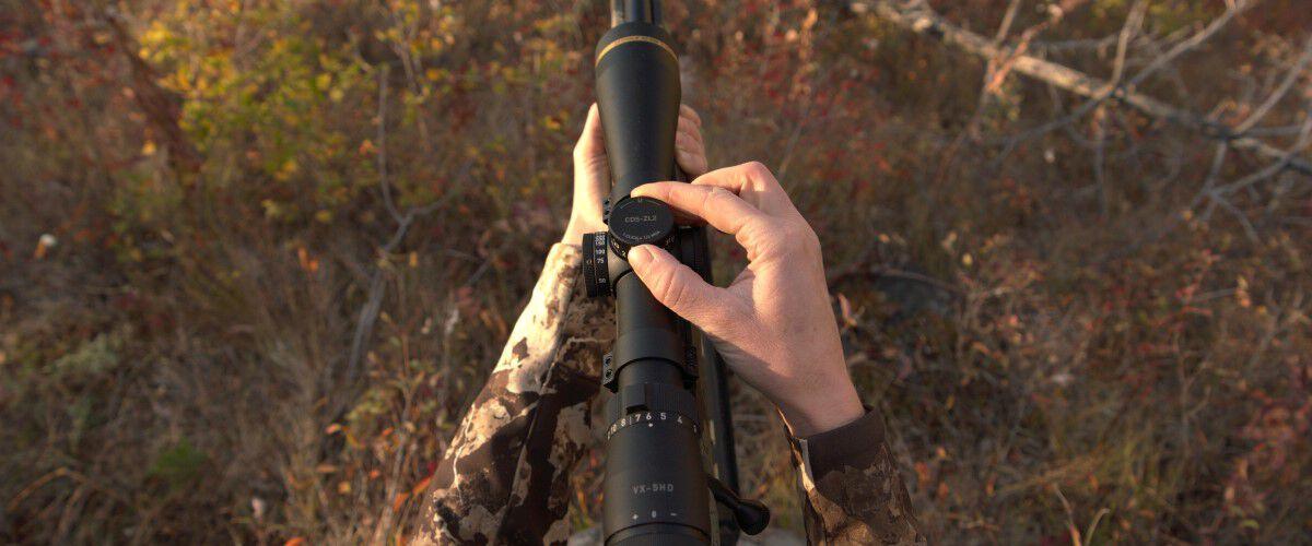 a hunter adjusting a rifle scope