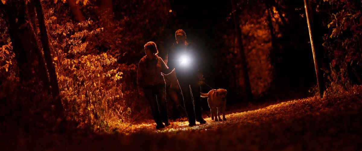 Man and Woman walking a dog in the dark while holding a flashlight