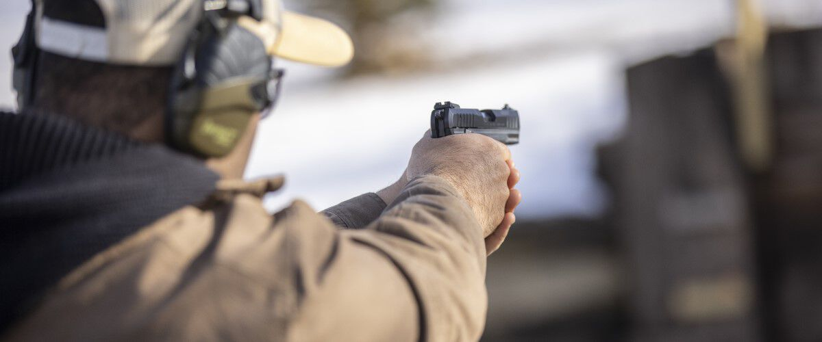 man pointing handgun outside