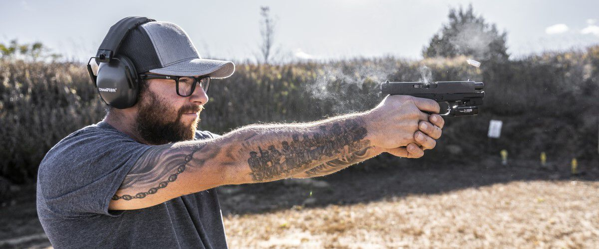 Person pointing a handgun outside