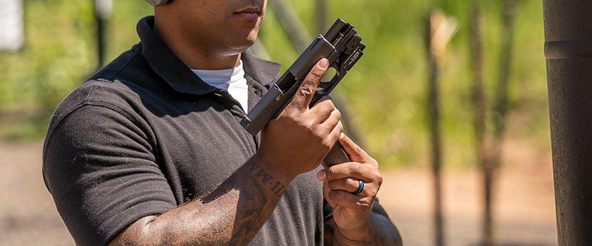 guy loading magazine into pistol
