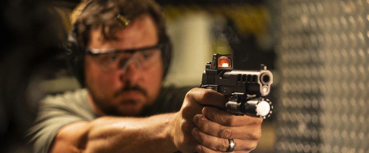 Person pointing a handgun in an indoor range