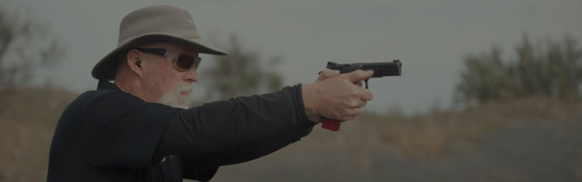 man pointing a pistol outside