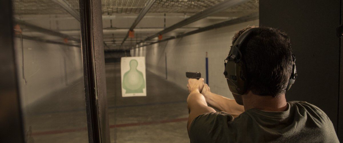 Man holding a pistol at an indoor range