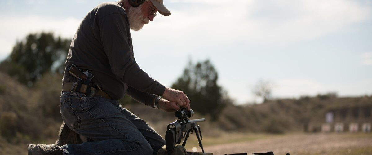 man getting rifle scope ready at an outdoor range