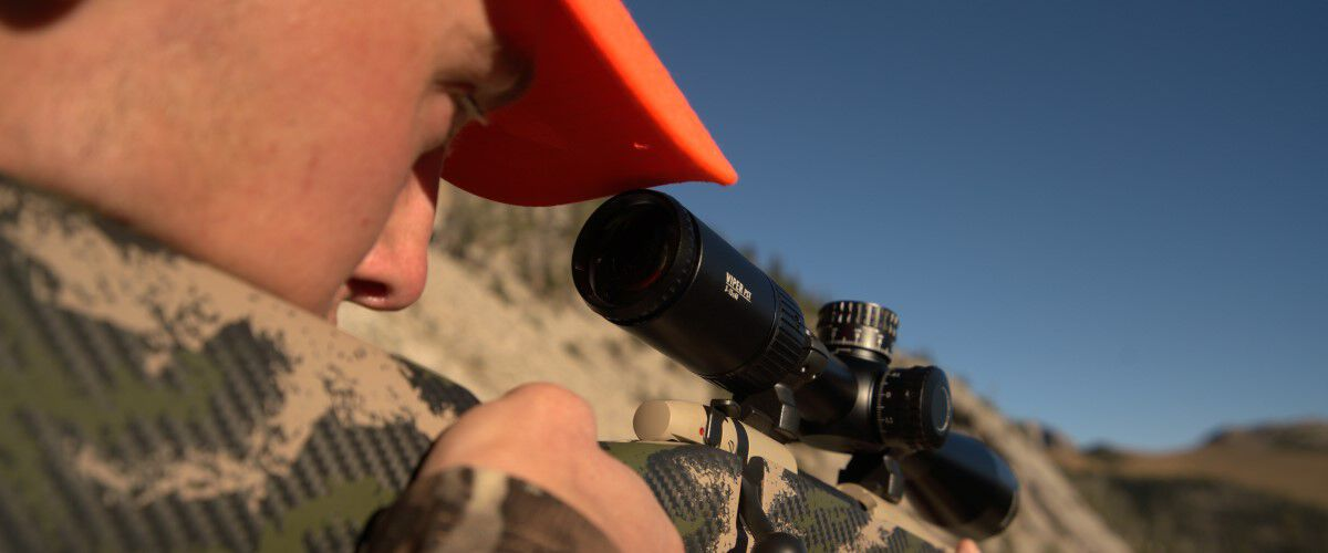 hunter looking down a rifle scope outside