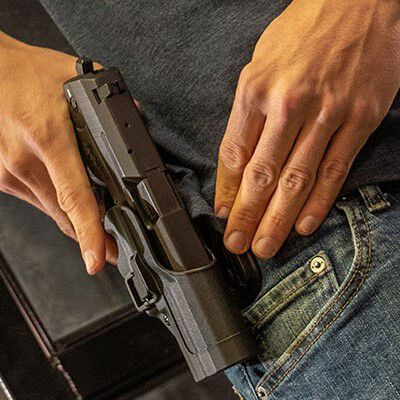 person putting pistol into a holster attached to their jeans
