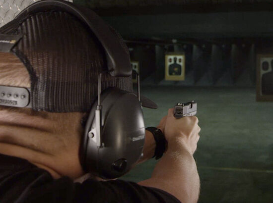 Person Shooting Handgun at Gun Range