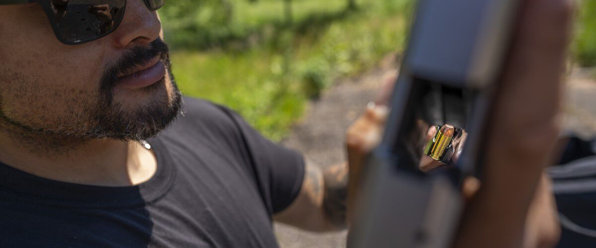 Man loading magazine into handgun