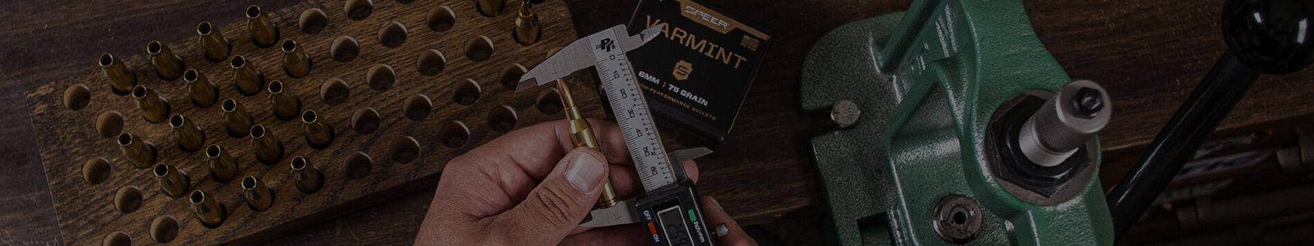 man measuring a loaded bullet