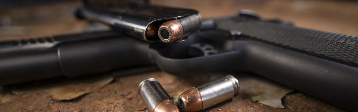 Speer bullets laying on a table beside a pistol