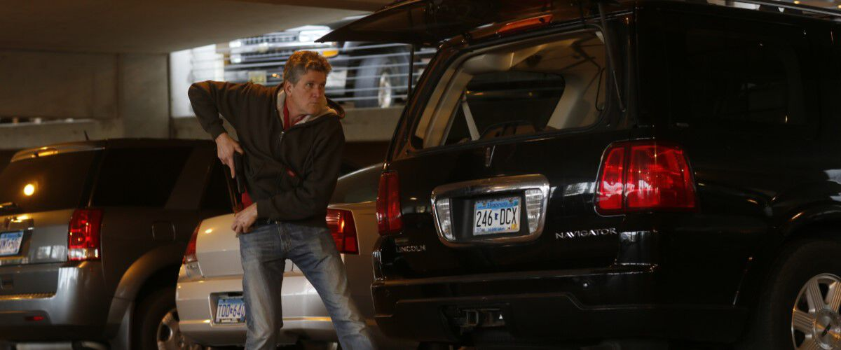 Man pulling a gun from under his jacket standing by his car in a parking ramp