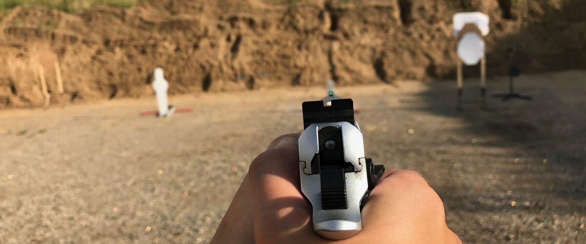 A handgun being pointed at an outdoor target